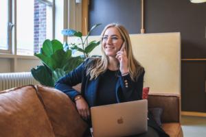Telefonierende Frau auf einem Sofa mit einem Laptop auf dem Schoß
