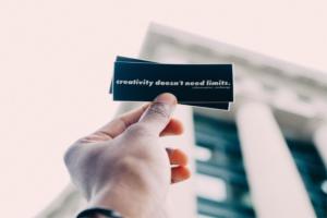 """Hand die ein Schild mit der Aufschrift """"creativity doesn't need limits."""" hält"""