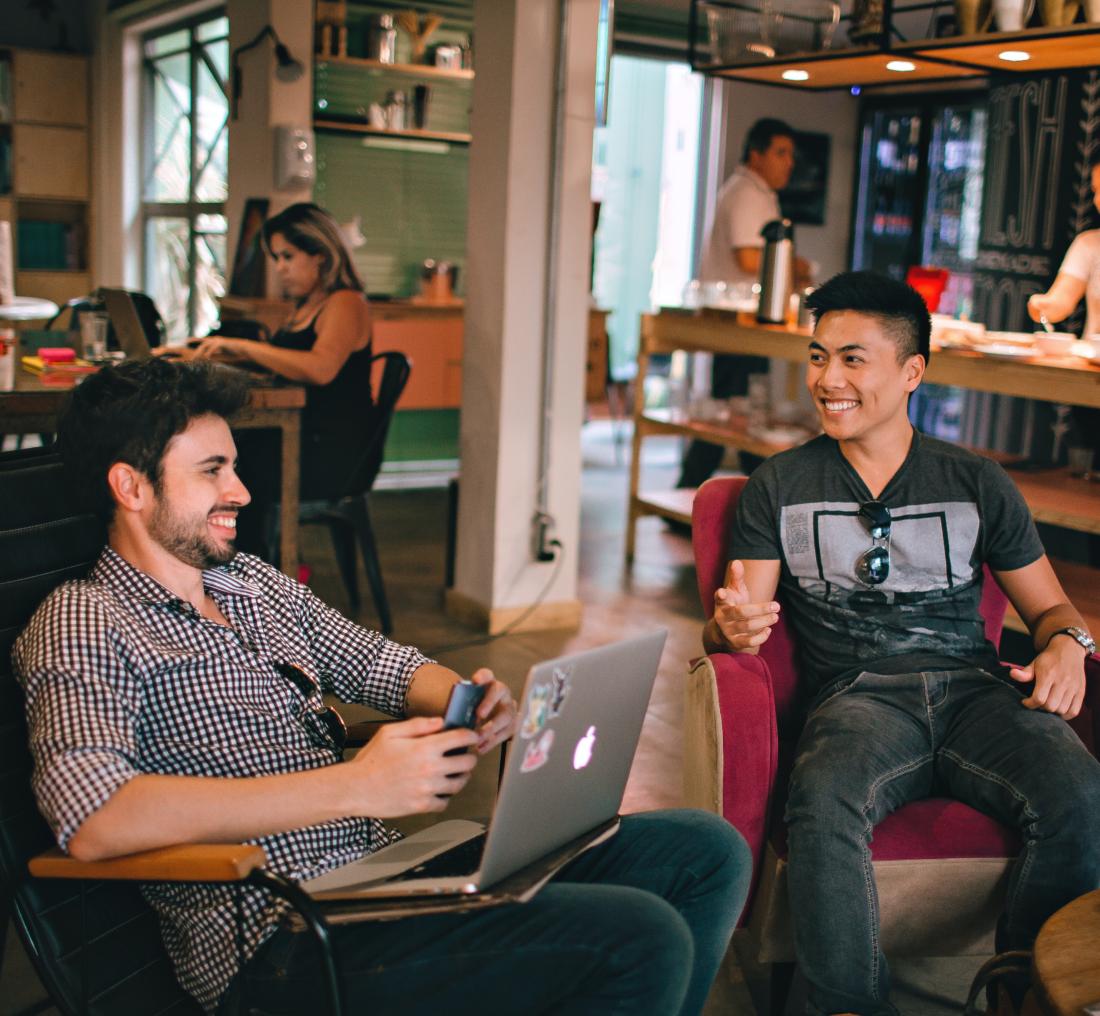 Zwei Männer, die in einem Café sitzen, arbeiten und sich amüsieren