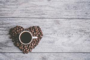 Kaffeetasse und ein aus Kaffebohnen geformtes Herz - Internationaler Tag des Kaffees