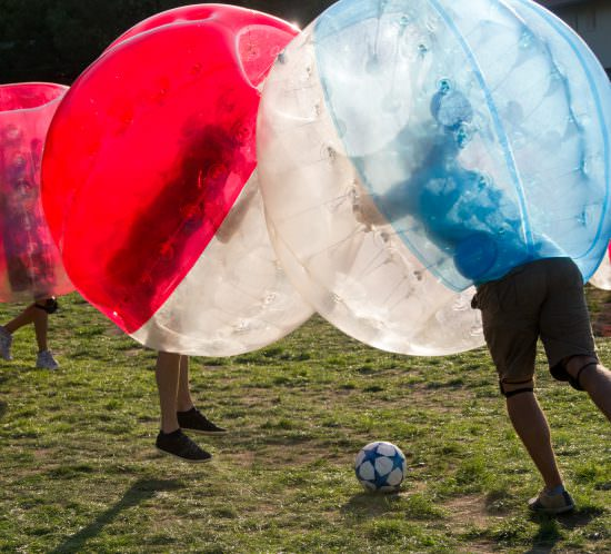 Teenagers play in Bubble bump, new and fun team game outdoor. Children are inside of blown plastic transparent bubble shock each other with fun. Out of focus park zone is at background